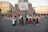 Riga, Latvia - August 23, 2015: Representations of the three Baltic countries wear traditional dress and hold their national flags in Riga, Latvia, during a 26th anniversary commemoration of the Baltic Way. Also called the Baltic Chain, the peaceful political demonstration took place on August 23, 1989. Approximately two million people held hands to form a human chain stretching 675.5 kilometres (419.7 mi) across Estonia, Latvia, and Lithuania, which at the time were part of the Soviet Union. For this anniversary, the Ukrainian flag was also invited.