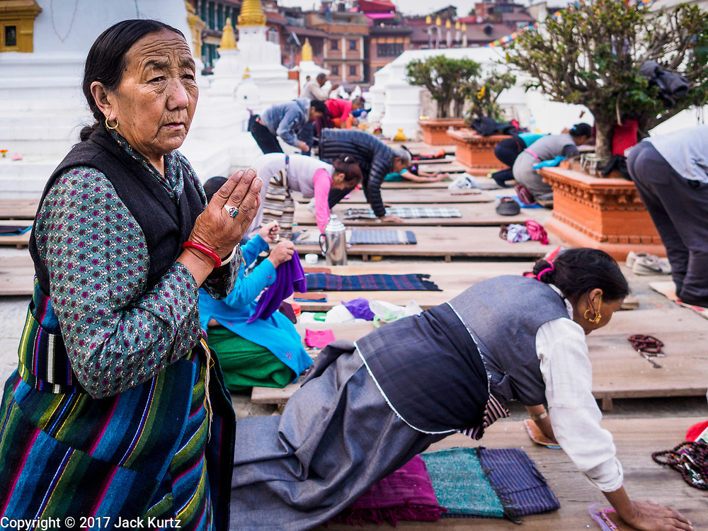 17 MARCH 2017 - KATHMANDU, NEPAL: People pray in front of Boudhanath Stupa in Kathmandu during morning prayers. The stupa is the holiest site in Nepali Buddhism. It is also the center of the Tibetan exile community in Kathmandu. The Stupa was badly damaged in the 2015 earthquake but was one of the first buildings renovated.     PHOTO BY JACK KURTZ