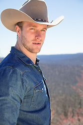 Portrait of a handsome blonde cowboy with blue eyes outdoors