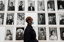 "© Licensed to London News Pictures. 03/11/2020. LONDON, UK. A staff members views works from the ongoing series ""Faces and Phases"". Preview of the first major UK exhibition by South African visual activist Zanele Muholi at Tate Modern.  260 photographs document black lesbian, gay, trans, queer and intersex lives in South Africa.  The show runs 5 November to 7 March 2021, but will be interrupted by England's coronavirus pandemic lockdown currently due to last 5 November to 2 December.    Photo credit: Stephen Chung/LNP"