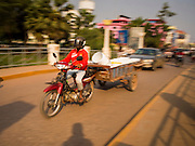 15 MARCH 2015 - SIEM REAP, SIEM REAP, CAMBODIA:  A motorcycle hauls a trailer on the bridge over the Siem Reap River on National Highway 6 in Siem Reap.    PHOTO BY JACK KURTZ