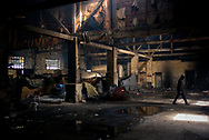 Inside one of the warehouses used as shelter by migrants in Belgrade train station. They sleep wrapped in wool blanket and warm up lighting bone fire inside the wearhouse. The air gets saturaded with smoke and unbreathable. Belgrade Serbia, March 20th, 2017. Federico Scoppa