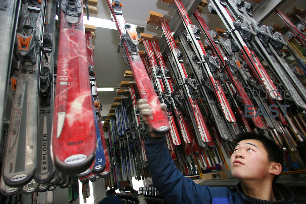NANSHAN, CHINA - January 23: An employee grabs skis for rent on January 23, 2006 in Nanshan ski resort, China. In Nanshan Ski Resort the snow is man-made and each of the 12 runs lasts less than a minute. (Photo by Servais Mont/Getty Images)