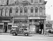 9903-503-01.  SW 2nd Ave., near the SW corner of Oak. Telephone company repair truck parked at curb.  From left to right, Yee San Tank co., The New Barber Shop. Hoy Sun Low Chinese Restaurant.  The barber has a sign that they will be moving from this location on August 31st, 1954.