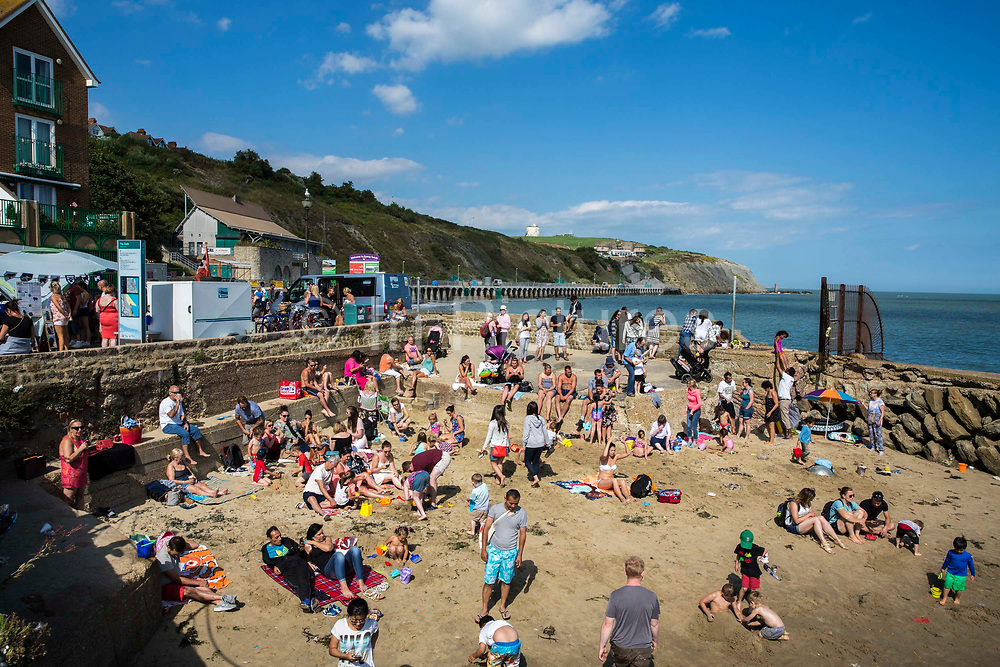 Lots of people play, relax and enjoy the sandy beach after the annual Trawler Race in Folkestone Harbour, Folkestone, Kent, England, United Kingdom.