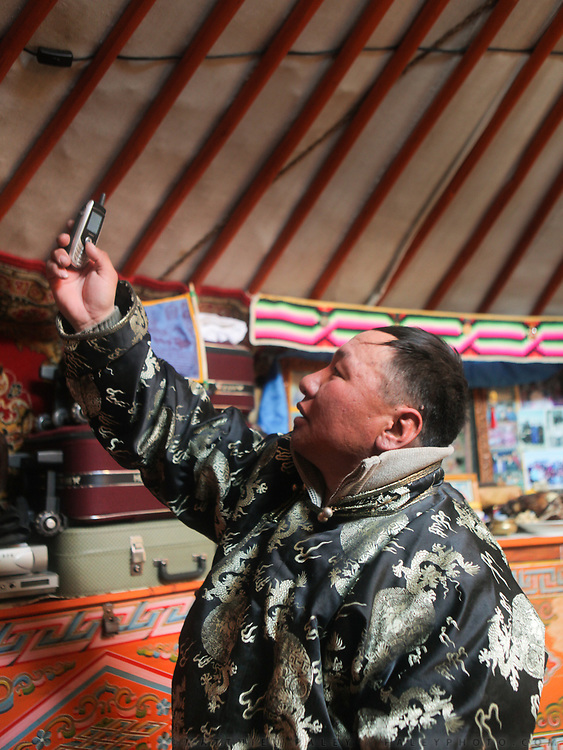 A mongolian man trying to get reception on his mobile phone, in a yurt. Road trip with a Jeep in the Gobi region.