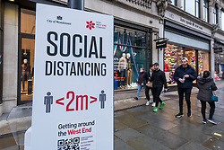 © Licensed to London News Pictures. 21/12/2020. LONDON, UK. People pass a social distancing sign in Regent Street in the West End as Tier 4, Stay at Home, alert level restrictions are imposed on much of the UK to combat the ongoing coronavirus pandemic in the light of a recently discovered mutant strain that was discovered in the south east of England.  Photo credit: Stephen Chung/LNP