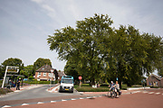 In Zevenaar passeren twee fietsers de bushalte voor het station waar een buurtbus klaar staat voor vertrek.<br /> <br /> In Zevenaar two cyclists pass the bus station.