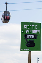 London, UK. 5th June, 2021. A Stop The Silvertown Tunnel placard is pictured beneath the Emirates Air Line cable car as environmental activists and local residents protest against the construction of the Silvertown Tunnel. Campaigners opposed to the controversial new £2bn road link across the River Thames from the Tidal Basin Roundabout in Silvertown to Greenwich Peninsula argue that it is incompatible with the UK's climate change commitments because it will attract more traffic and so also increased congestion and air pollution to London's most polluted borough.