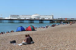 © Licensed to London News Pictures. 29/07/2014. Brighton, UK. people relaxing and sunbathing on Brighton beach. The weather has returned to sunny and hot after yesterday morning's torrential rains with temperatures expected to reach around the 23C in Brighton and the South Coast. Photo credit : Hugo Michiels/LNP
