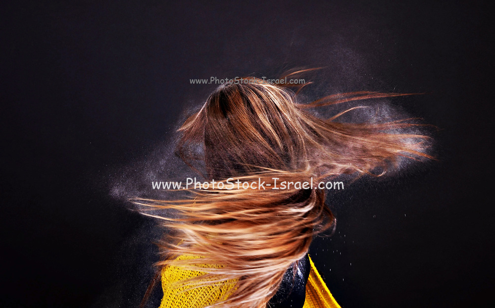 Powder blows out of twirling woman's hair
