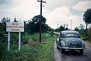 Morris Minor car on road landward side of Pitch Lake with pitch creep crossing warning sign notice, Trinidad c 1962