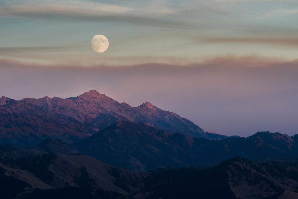 The moon rises above the mountains surrounding Jackson Wyoming as the sun sets below Teton Pass.