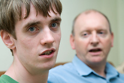 Teenage boy with Autism with his father in the background,