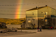 A moment of magic light in the village, with a rainbow falling behind the hill.