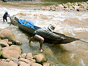 Boatman So and his son Somvang push their boat through shallow rapids on the Nam Ou river during the dry season when the river level is low, Phongsaly province, Lao PDR. The Nam Ou river connects small riverside villages and provides the rural population with food for fishing. But this river and others like it, that are the lifeline of rural communities and local economies are being blocked, diverted and decimated by dams. The Lao government hopes to transform the country into 'the battery of Southeast Asia' by exporting the power to Thailand and Vietnam.