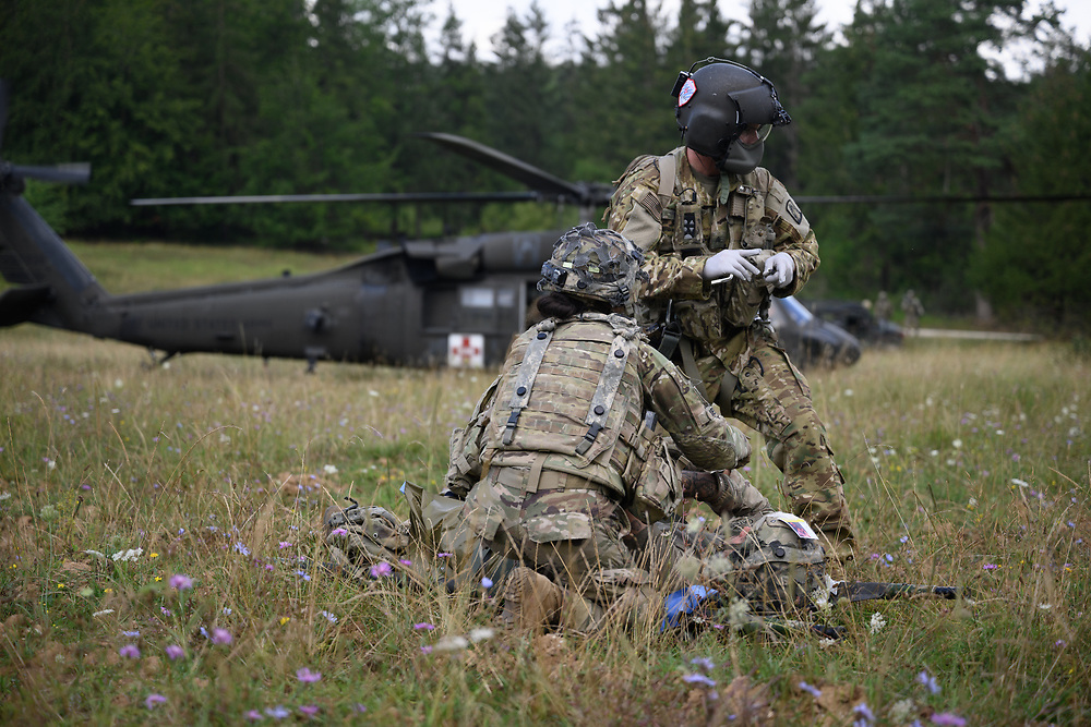 U.S. Army Sgt. Derek Born from Charlie Company, 1st Battalion, 214th Aviation Regiment assesses patients at a mass casualty exercise during Saber Junction 20, Aug. 15, 2020, at Hohenfels Training Area. Saber Junction 20 is a 7th Army Training Command-conducted, U.S. Army Europe-directed annual exercise designed to assess the readiness of the U.S. Army's 173rd Airborne Brigade to execute unified land operations in a joint, combined environment, and to promote interoperability with participating allies and partner nations. This year's exercise will take place primarily at 7ATC's Grafenwoehr and Hohenfels Training Areas in Bavaria. U.S. military forces stationed in Europe routinely conduct these types of exercises with allied and partner nations to enhance interoperability and readiness. (U.S. Army photo by Sgt. 1st Class Garrick W. Morgenweck)