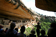"""Park Ranger Amanda Kuhnel (right standing and pointing), 23, points out some of the features of the Cliff Palace dwelling during an hour-long tour at Mesa Verde National Park near Cortez, Co. on Wednesday June 28, 2006. It is Kuhnel's first year working at the park and said the National Park Service had hired additional interpretive guides in the park this summer to handle the increased number of visitors for its 100th birthday. She said, """"my tours have all been sold out"""". On June 29, 1906 Theodore Roosevelt designated Mesa Verde a national park, the first cultural national park in the history of the world. The park will celebrate it's 100th birthday with a weekend of events, dancing, musical entertainment and special tours of some of the cliff dwellings. Cilff Palace is the largest of all the dwellings at Mesa Verde with 150 rooms and 21 kivas..(MARC PISCOTTY/ © 2006)"""