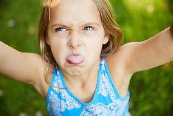 Close up of Young Girl Sticking out tongue Outdoors