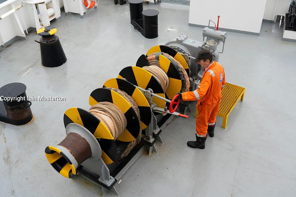 Man operating windlass machinery during berthing of Northlink ferry between Shetland and Aberdeen, Scotland UK