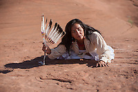 Native american woman touching sacred ground. Native American Navajo Woman Yogini. Diné woman practicing yoga in her indigenous red earth environment.