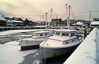 Annapolis, Maryland--Work boats take safe harbor from the cold winter waters of the Chesapeake Bay at City Dock in Annapolis. In the harshest winters, Annapolis has opened is harbor to the waterman who work the bay dredging and raking for oysters and clams. With its close proximity to the bay, waterman usually have a safe iceless pasasge to the oyster and clam beds.