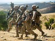 Three Marines carry AT-4 rockets under the watchful eye of Sgt. Fowlkes during live-fire exercises for the 2nd Battalion, 5th Marine Regiment at Camp Pendleton.