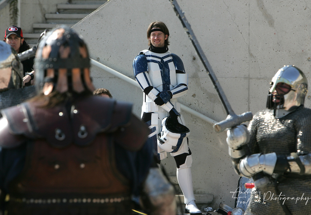"""Andrew Foulk/ Zuma Press.July 24, 2009, San Diego, California, USA. Comic Con.A lone """" Storm Trooper""""  watches as a group of renaissance re-enactors do battle out side the San Diego convention center , during day two of the 40th annual San Diego International Comic Con."""