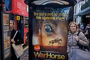 Women shoppers at a bus stop with a War Horse poster in central London. The women are in the busy Oxford Street shopping street and bus stop posters are a popular method of advertising media, promoting West End stage productions etc. While one women on the left consults a bus route map of the capital, the lady on the right looks beyond to or perhaps another shop to visit in the weeks before Christmas.