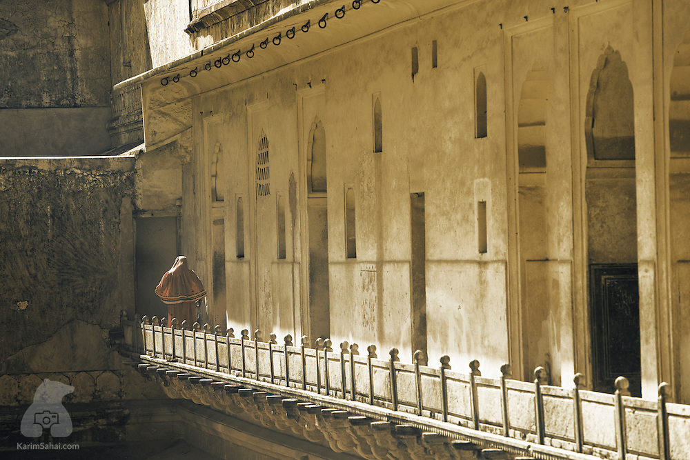 A woman walks on a balcony at the Amer Fort in Jaipur, Rajasthan, India.