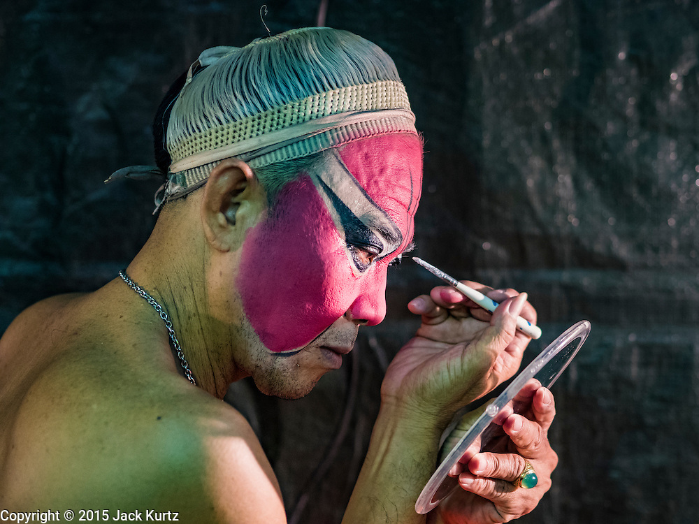 15 OCTOBER 2015 - BANGKOK, THAILAND: A Chinese opera performer works on his eye make up before performing at the Vegetarian Festival at the Joe Sue Kung Shrine in the Talat Noi neighborhood of Bangkok. The Vegetarian Festival is celebrated throughout Thailand. It is the Thai version of the The Nine Emperor Gods Festival, a nine-day Taoist celebration beginning on the eve of 9th lunar month of the Chinese calendar. During a period of nine days, those who are participating in the festival dress all in white and abstain from eating meat, poultry, seafood, and dairy products. Vendors and proprietors of restaurants indicate that vegetarian food is for sale by putting a yellow flag out with Thai characters for meatless written on it in red. The shrine is famous for the Chinese opera it hosts during the Vegetarian Festival. The operas are free.    PHOTO BY JACK KURTZ