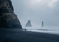 Reynisfjara black sand beach on a stormy winter morning. Lone tourist standing on beach. South Iceland.