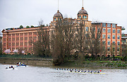 """Hammersmith, Greater London, 15th March 2020, Inaugural Men's Lightweight Boat Race, Oxford University Lightweight Women, [Blue Boat], take half a length, over Cambridge University Lightweight Men's BC, as both crews pass, """"Harrods Village"""". William Hunt Mansions, AKA Harrods Depository, on the approach to Hammersmith Bridge, Championship Course, Putney to Mortlake, River Thames, [Mandatory Credit: Peter SPURRIER/Intersport Images],"""