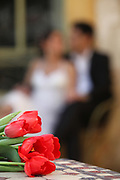 Wedding Concept Bridal flower bouquet with an out of focus bride and groom in the background