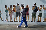 Outside a shop under refit a hoarding depicting members of the public engaging with their digital handheld devices as real people pass by in London, England, United Kingdom.
