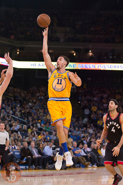 November 17, 2015; Oakland, CA, USA; Golden State Warriors guard Klay Thompson (11) shoots the basketball against the Toronto Raptors during the third quarter at Oracle Arena. The Warriors defeated the Raptors 115-110.