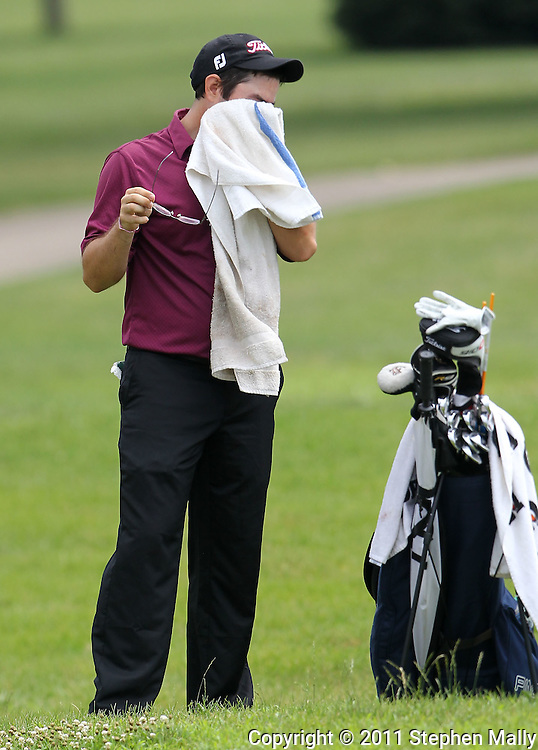 Philip Arouca of Wilmette, Illinois wipes off his sweat on a towel on the eighteenth hole during the second round of the Greater Cedar Rapids Open held at Hunters Ridge Golf Course in Marion on Saturday, July 23, 2011.