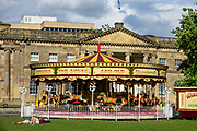 What British call a roundabout is a merry-go-round or carousel in American English (from French carrousel and Italian carosello), invented by Paul Bussler as an amusement ride. A carousel has a rotating circular platform with seats for riders, traditionally as rows of wooden horses or other animals mounted on posts, many of which move up and down by gears to simulate galloping, to the accompaniment of circus music. Photographed in front of the Castle Museum in York, North Yorkshire, England, United Kingdom, Europe.