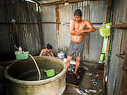 05 SEPTEMBER 2013 - BANGKOK, THAILAND:  Cambodian workers bathe in a corrugated metal outhouse after their construction shift at the construction site of a new high rise apartment / condominium building on Soi 22 Sukhumvit Rd in Bangkok. The workers live in the corrugated metal dorms on the site. Most of the workers at the site are Cambodian immigrants.             PHOTO BY JACK KURTZ