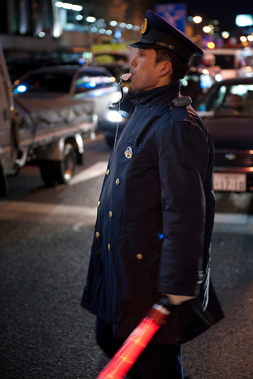 A policeman directing gridlocked traffic. Shinagawa, Tokyo, 11 March 2011. After a huge earthquake in north-east Japan several million people in Tokyo struggle to return home.