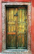 Locked wood door, red wall, Santorini Island, Greece, Europe.