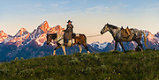 Wrangler and his horses crossing the ridge line in early morning light with the Teton mountain peaks as a backdrop in Jackson Hole, WY.