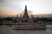 "07 MARCH 2009 -- BANGKOK, THAILAND: A sunset cruise passes Wat Arun, a Buddhist temple (wat) in the Bangkok Yai district of Bangkok, Thailand, on the west bank of the Chao Phraya River. The full name of the temple is Wat Arunratchawararam Ratchaworamahavihara. The outstanding feature of Wat Arun is its central prang (Khmer-style tower). It may be named ""Temple of the Dawn"" because the first light of morning reflects off the surface of the temple with a pearly iridescence. Steep steps lead to the two terraces. The height is reported by different sources as between 66,80 m and 86 m. The corners are surrounded by 4 smaller satellite prangs. The prangs are decorated by seashells and bits of porcelain which had previously been used as ballast by boats coming to Bangkok from China. The central prang is topped with a seven-pronged trident, referred to by many sources as the ""trident of Shiva"". Around the base of the prangs are various figures of ancient Chinese soldiers and animals. Over the second terrace are four statues of the Hindu god Indra riding on Erawan. The temple was built in the days of Thailand's ancient capital of Ayutthaya and originally known as Wat Makok (The Olive Temple). In the ensuing era when Thonburi was capital, King Taksin changed the name to Wat Chaeng. The later King Rama II. changed the name to Wat Arunratchatharam. He restored the temple and enlarged the central prang. The work was finished by King Rama III. King Rama IV gave the temple the present name Wat Arunratchawararam. As a sign of changing times, Wat Arun officially ordained its first westerner, an American, in 2005. The central prang symbolizes Mount Meru of the Indian cosmology. The satellite prangs are devoted to the wind god Phra Phai. Photo By Jack Kurtz"