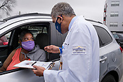 27 MARCH 2021 - DES MOINES, IOWA: Dr. YOGESH SHAH, Chief Medical Officer and Vice President of Medical Affairs at Broadlawns Medical Center, talks to PAM SPENCER about the COVID-19 vaccination he is about to get, during a COVID-19 (Coronavirus) vaccination clinic at Corinthian Baptist Church in Des Moines, Saturday. The clinic was organized by Broadlawns Medical Center and the United Way and provided more than 1,100 shots to Des Moines area residents. The clinic was a part of an effort to reach communities of color in Iowa, who are vaccinated at rates below the state average.       PHOTO BY JACK KURTZ