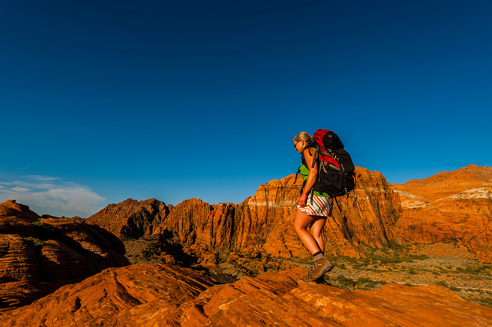 Woman backpacking in the red rock formations of Snow Canyon State Park near St. George, Utah USA.