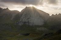Sun breaks though clouds over rocky face of Breiflogtind, Moskenesøy, Lofoten Islands, Norway