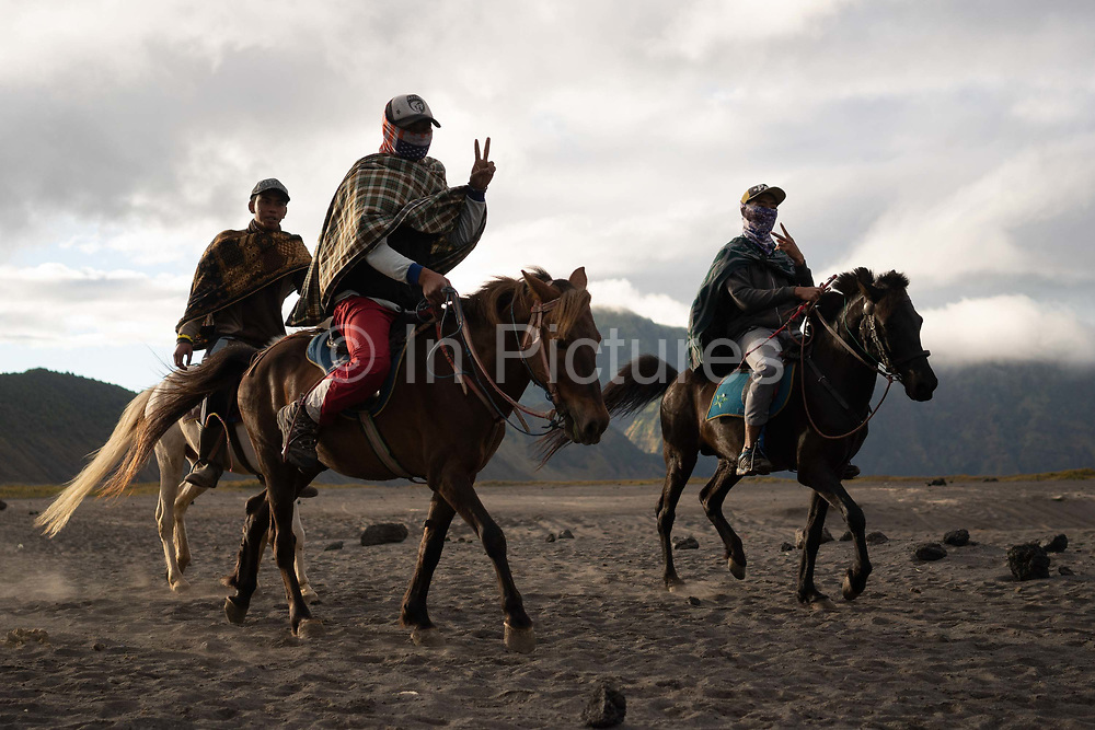 Indonesian Javanese men on horseback ride past Mount Bromo Gunung Bromo at dawn on 11th June 2018, East Java, Indonesia. The active volcano is park of the Bromo Tengger National Park, sitting on a plain called the sea of sand, it is possible to look into the crater of the volcano to see the smoke and steam emerging from it, lava is not visible.