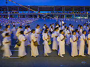 """22 FEBRUARY 2016 - KHLONG LUANG, PATHUM THANI, THAILAND: People participate in the procession around the chedi during the Makha Bucha Day service at Wat Phra Dhammakaya.  Makha Bucha Day is a public holiday in Cambodia, Laos, Myanmar and Thailand. Many people go to the temple to perform merit-making activities on Makha Bucha Day, which marks four important events in Buddhism: 1,250 disciples came to see the Buddha without being summoned, all of them were Arhantas, Enlightened Ones, and all were ordained by the Buddha himself. The Buddha gave those Arhantas the principles of Buddhism, called """"The ovadhapatimokha"""". Those principles are:  1) To cease from all evil, 2) To do what is good, 3) To cleanse one's mind. The Buddha delivered an important sermon on that day which laid down the principles of the Buddhist teachings. In Thailand, this teaching has been dubbed the """"Heart of Buddhism."""" Wat Phra Dhammakaya is the center of the Dhammakaya Movement, a Buddhist sect founded in the 1970s and led by Phra Dhammachayo.      PHOTO BY JACK KURTZ"""