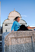 Child (9 years old) sitting on ancient Roman ruins, Church of St. Mary (Crkva Sveti Marije) in background, in late afternoon sunlight. Zadar, Croatia