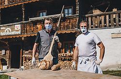 THEMENBILD - am Karfreitag backen Hans Jäger (Initiator Meixnerhaus) und Günther Katschner (Bäckerei Gugglberger) zum ersten Mal im Jahr Bauernbrot und Milchbrot bzw. Osterstriezel, im alten, traditionellen Holzofen neben dem Meixnerhaus am Kirchbichl oberhalb von Kaprun. Während der Corona-Virus-Krise tragen beide Mundschutz und Handschuhe aus Sicherheitsgründen, aufgenommen am 10. April 2020 in Kaprun, Oesterreich // on Good Friday Hans Jäger (initiator Meixnerhaus) and Günther Katschner (Bäckerei Gugglberger) bake farmhouse bread and milk bread or Osterstriezel for the first time in the year, in the old, traditional wood oven next to the Meixnerhaus at the Kirchbichl above Kaprun. During the corona virus crisis, both wear face masks and gloves for safety reasons, in Kaprun, Austria on 2020/04/10. EXPA Pictures © 2020, PhotoCredit: EXPA/Stefanie Oberhauser